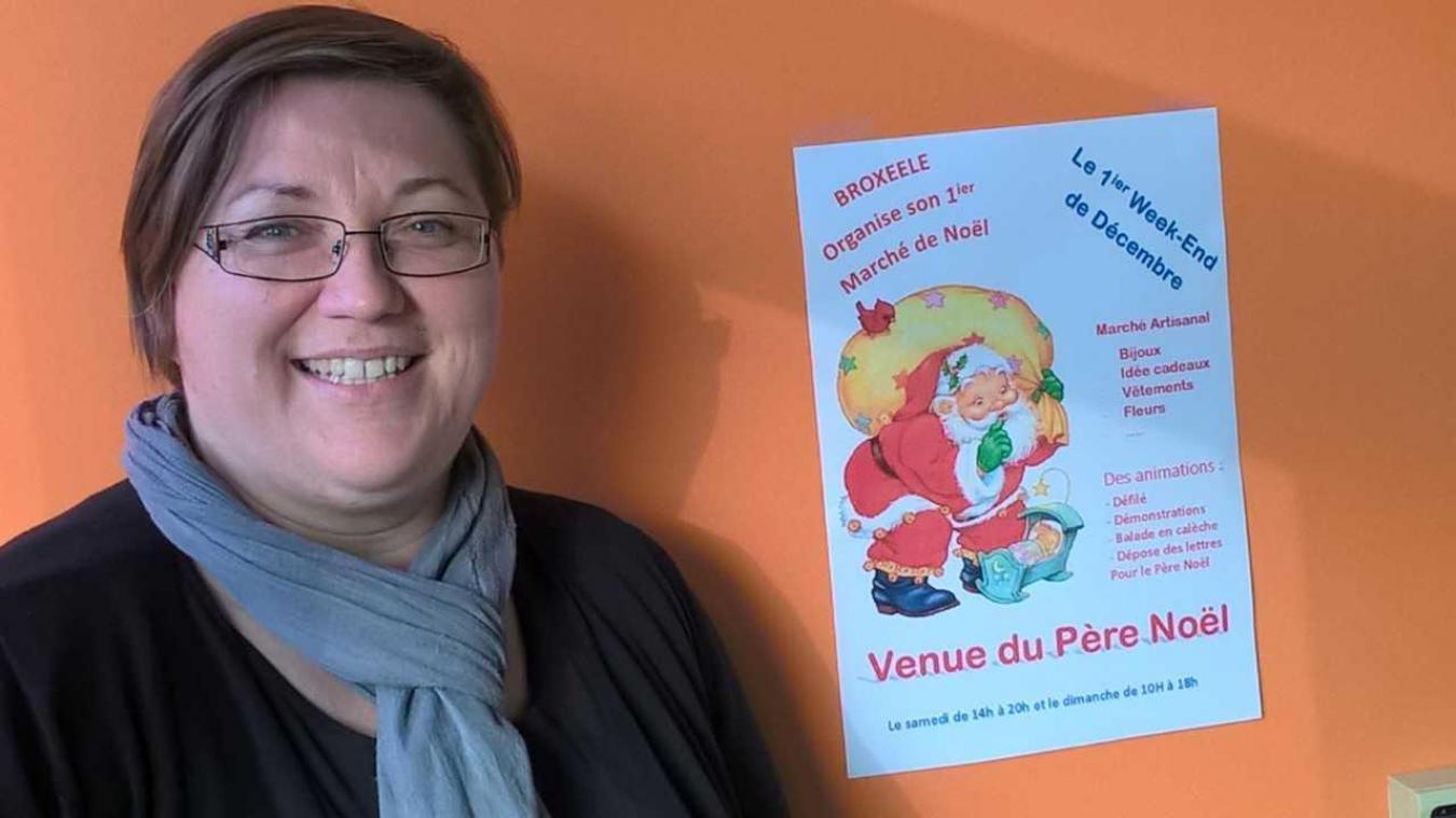 La présidente du comité des fêtes, Séverine Pietersoone, présentant fièrement l'affiche du premier marché de Noël du village.