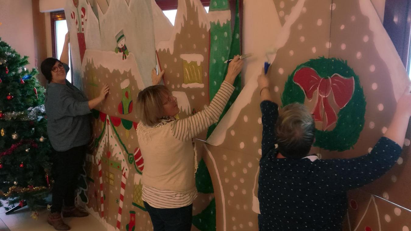 Laëtitia, sa mère et une amie préparent les décors sur le thème pain d'épice pour le marché de Noël de Bambecque.