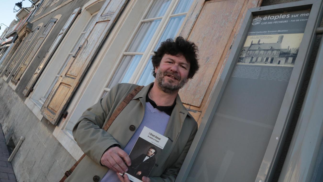 Jean-Christophe Macquet pose avec son 20 e  roman devant l'hôtel particulier Souquet-Marteau.