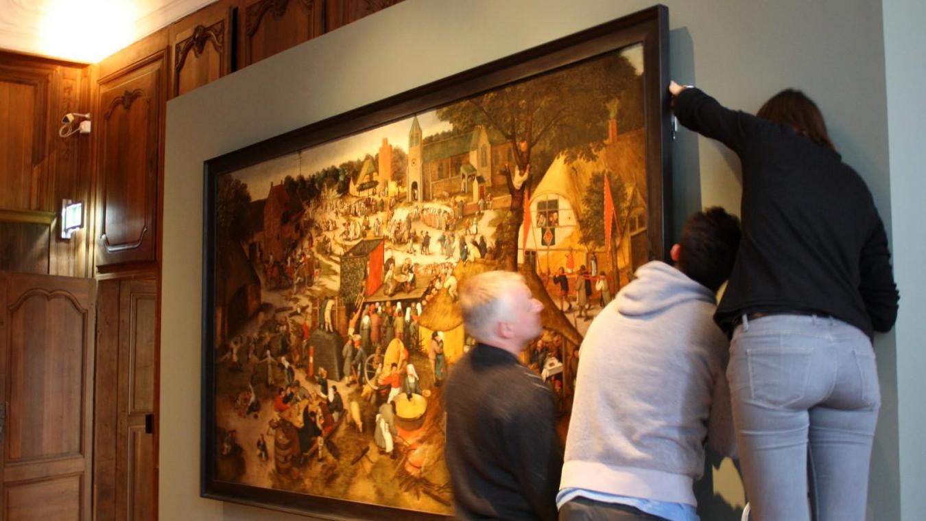 Accrochage, avec maintes précautions, de la première œuvre :  La Kermesse villageoise avec un théâtre et une procession  de Pieter II Brueghel. Cette huile sur toile de 152 x 283 cm, est un prêt du Musée Calvet d'Avignon.