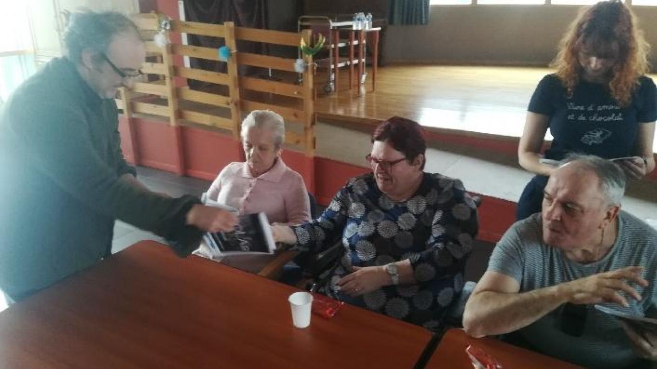 Après avoir travaillé dur, les résidents de l'Ehpad découvrent leur roman avec l'auteur à gauche.