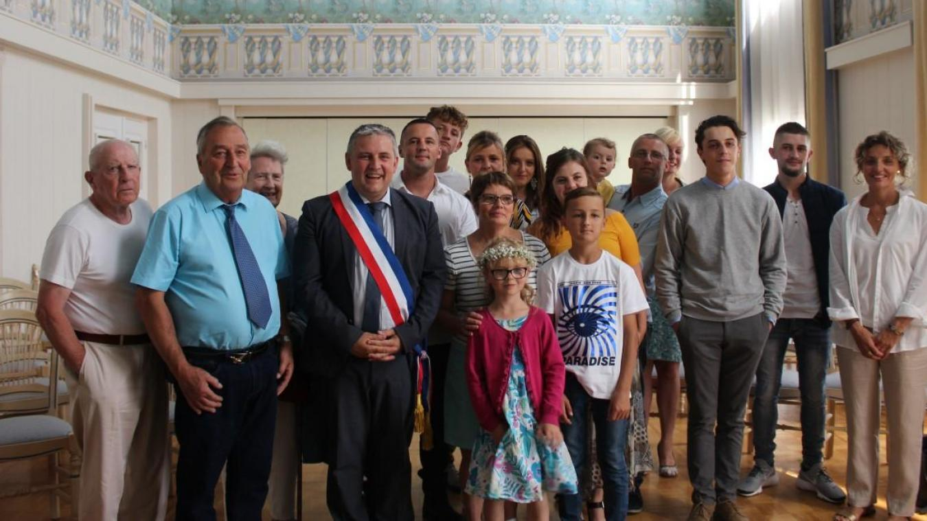 Angèle et Lucien Lebon, de chaque côté du maire Sébastien Chochois, entourés de leur famille pour célébrer leurs noces d'or.
