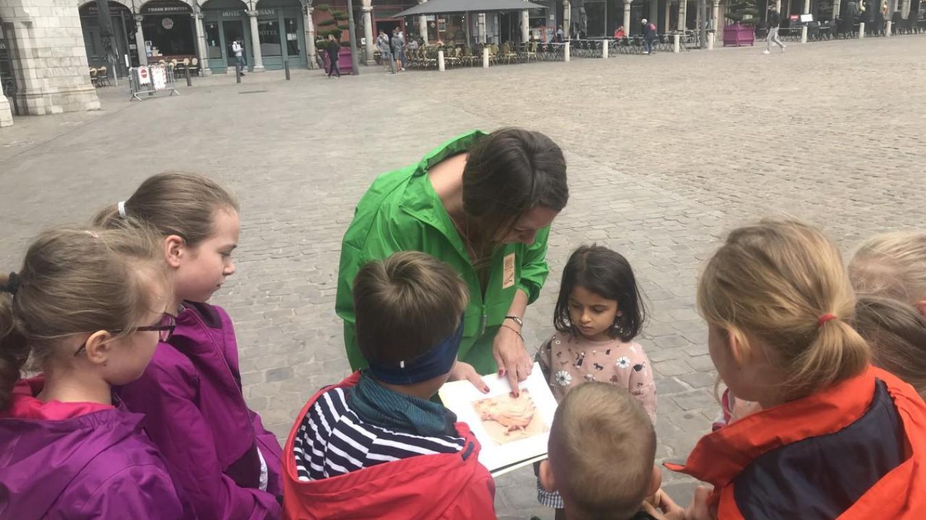 Aurélie Vilcocq invite les enfants à regarder des photos des animaux sculptés sur les façades, avant de les chercher.