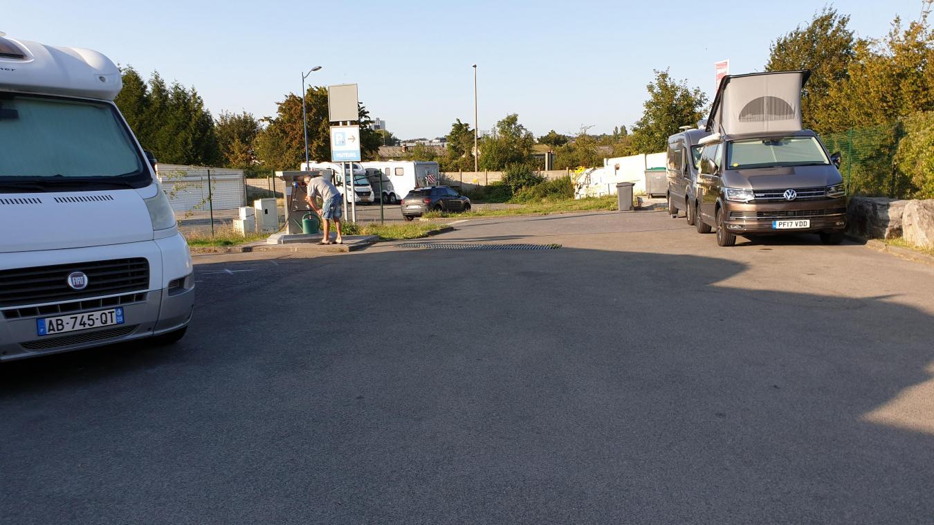 Mercredi 21 août en soirée, l'aire est pleine. Deux utilitaires se sont stationnés de manière perpendiculaire au stationnement régulier en épi. Dans le fond, deux camping-car ont choisi de se garer à l'extérieur de l'aire.