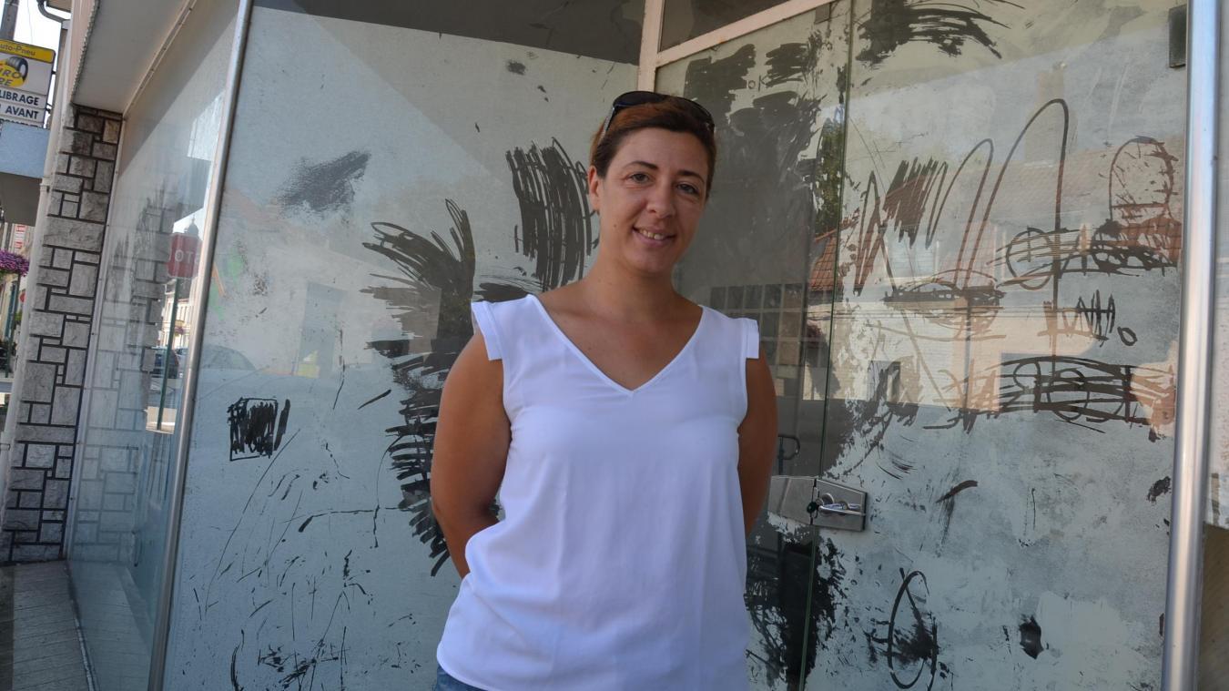 Cathy Bringuez pose devant la devanture de son future magasin de vêtements et d'accessoires de mode.