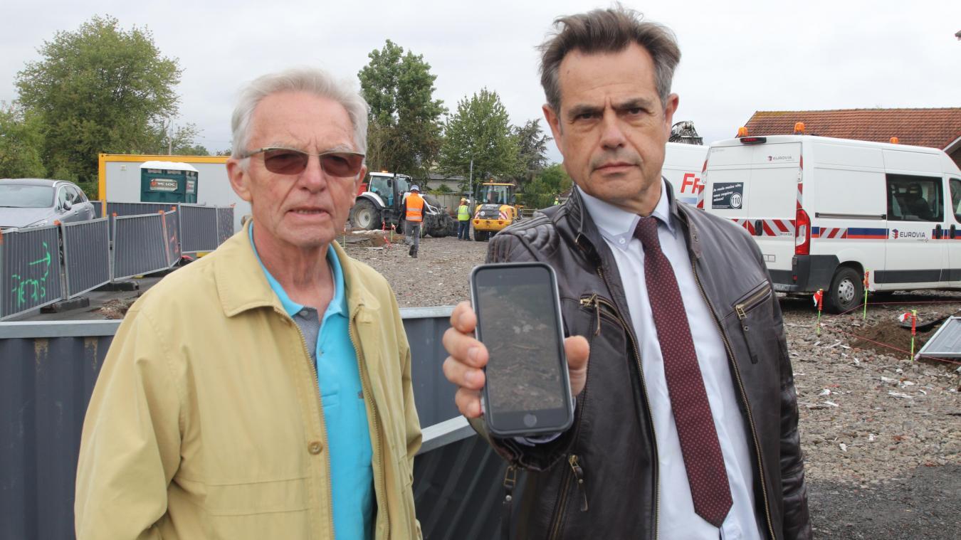 Sur le chantier du Centre, Marc Uberti (à droite), en compagnie de l'ancien maire Jean Clarisse, montre les photos des ossements découverts sur le chantier. Les ouvriers présents ont affirmé que ces ossements n'avaient pas été découverts sur place.