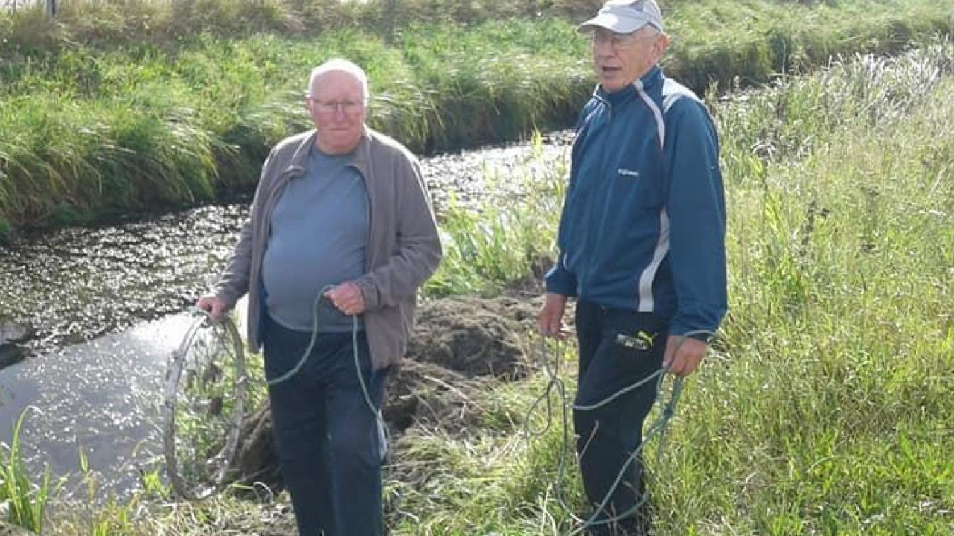 Les deux amis pêcheurs doivent régulièrement nettoyer le canal avant de pêcher. Une roue de vélo et du barbelé leur servent d'outils.
