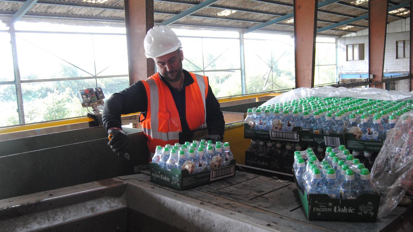 Les bouteilles d'eau circulent jusqu'à un séparateur dans lequel sont triés plastique et liquide.