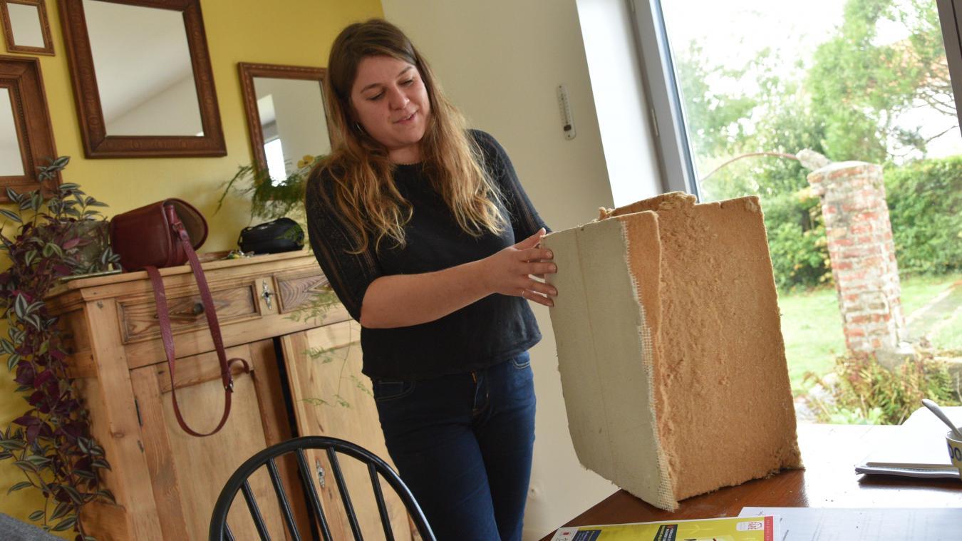 Mélanie Calcoen montre l'épaisseur de l'isolation extérieure en fibre de bois, qui permet de réduire considérablement les déperditions de chaleur.