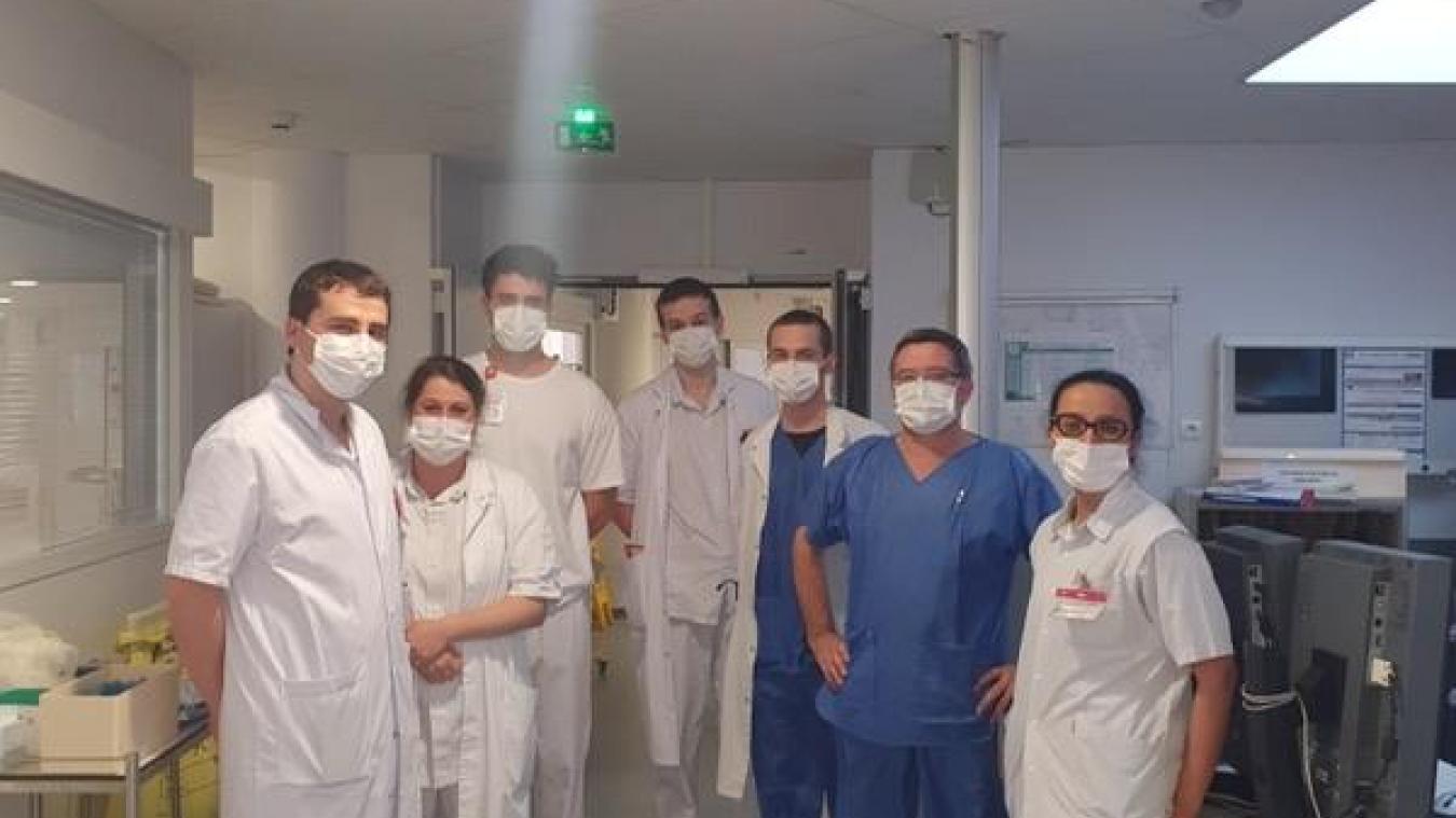 Une partie de l'équipe du service réanimation de l'hôpital pose en gardant le sourire derrière leur masque de protection