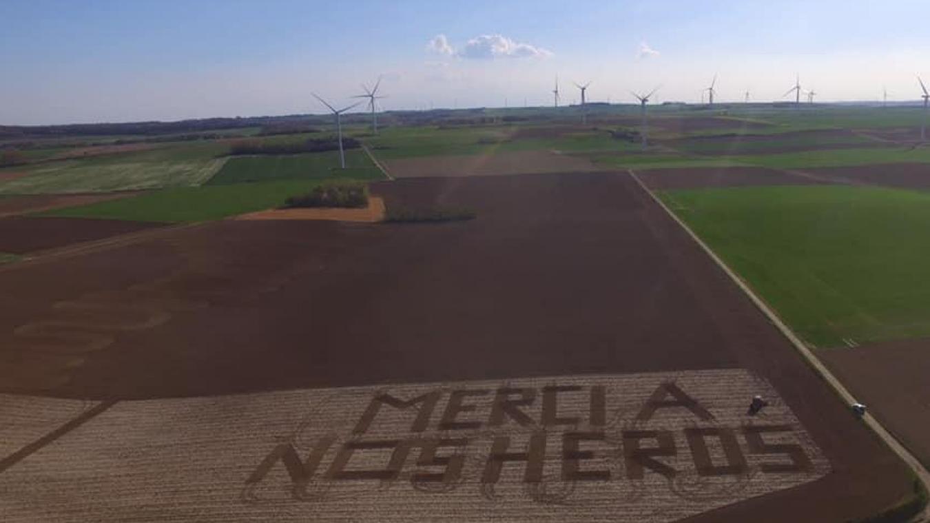 Alexis Bultel, Antoine Massart, Pierre Dupuis ont tracé leur message à Enguinegatte, dans un champ de culture au pied des éoliennes, au loin, sur le plateau.