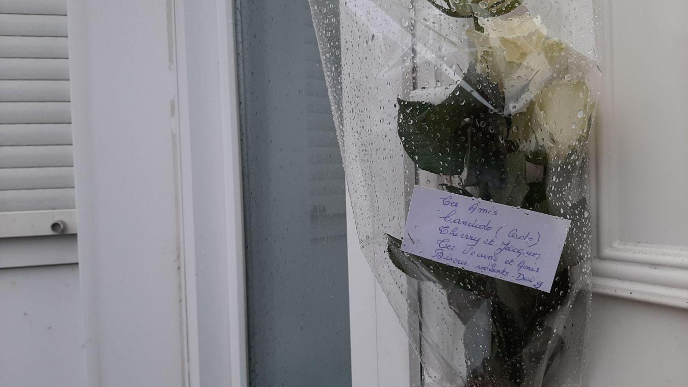 Des proches et voisins ont laissé un mot ainsi qu'un bouquet de fleurs sur la porte du domicile de la victime, au lendemain de la découverte du corps.