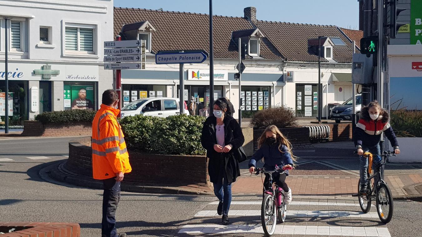 Des agents municipaux sécurisent les traversées des routes pour les familles.