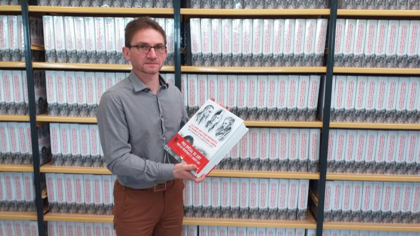 Laurent Thiery pose devant les centaines d'exemplaires du livre qui attendent de retrouver des familles de déportés.