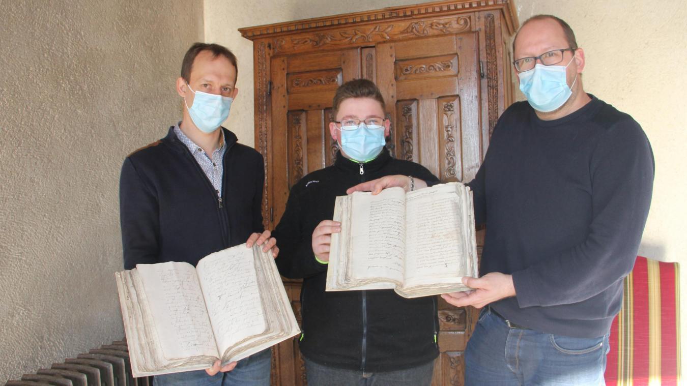 Christophe Delbecque (à gauche) et Hervé Devassine et son fils présentent les deux registres achetés aux enchères.