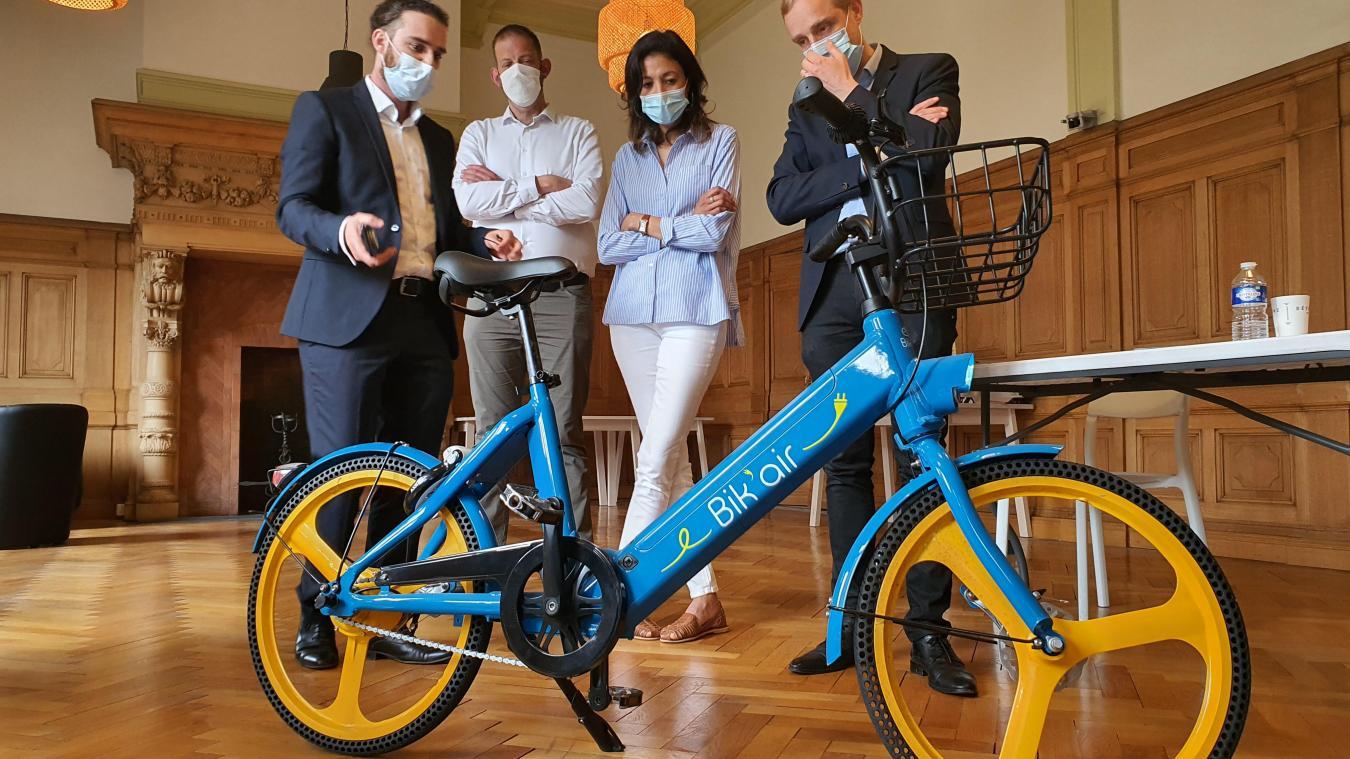 Nathan Cohen (à gauche de l'image) présente l'utilisation de son vélo jaune et bleu, Bik'air, à Olivier Gacquerre, maire de Béthune.