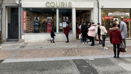 Devant le magasin de chaussures Courir, les clients sont invités à faire la queue pour respecter la distanciation sociale dans le magasin.